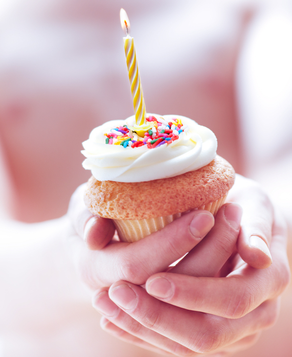Young man holding a cupcake with a single candle. Very shallow depth of field, the focus is on the candle only.